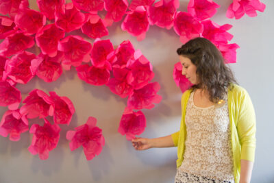 woman standing in front of a paper flower wall