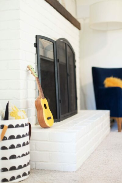 White painted brick fireplace with ukulele