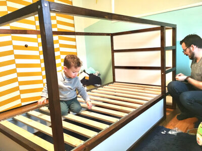 Son helping dad put bed together
