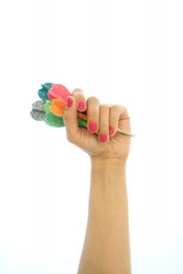 Hand with pink nail polish holding darts