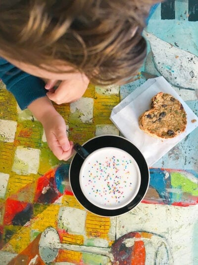 Little boy at coffee shop with sprinkles in his milk