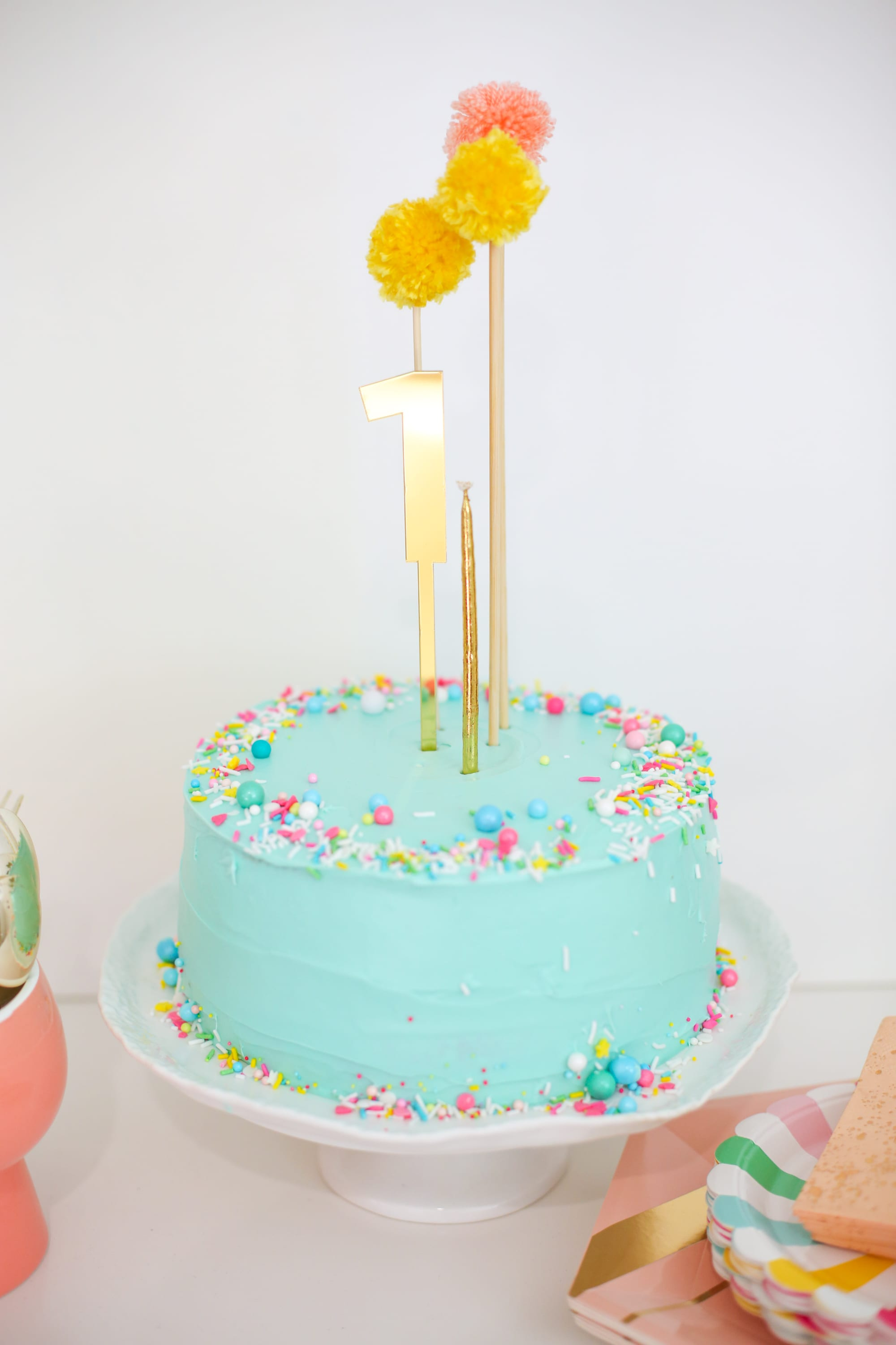Make a sprinkle cake with a pompom cake topper
