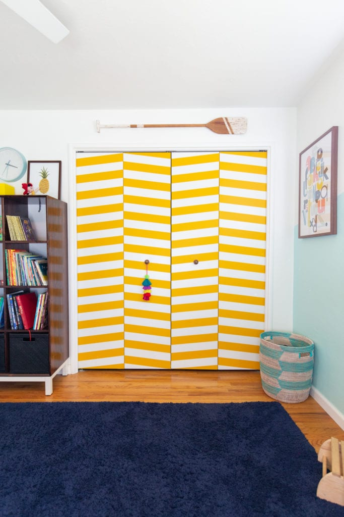 clean kids room in house with yellow closet doors