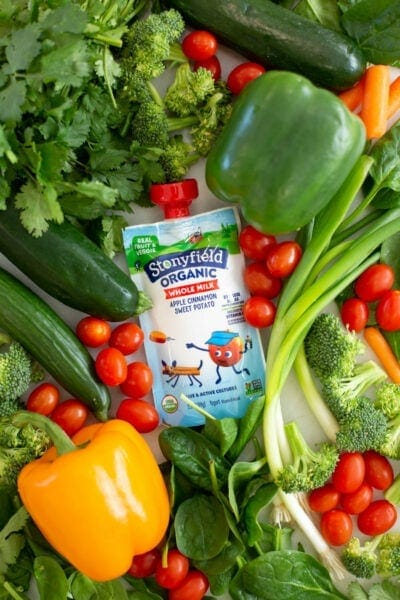 Yogurt pouch laying on a bed of vegetables
