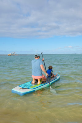 Father and daughter paddleboarding in Kauai