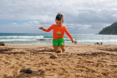 Boy jumping on Kauai beach