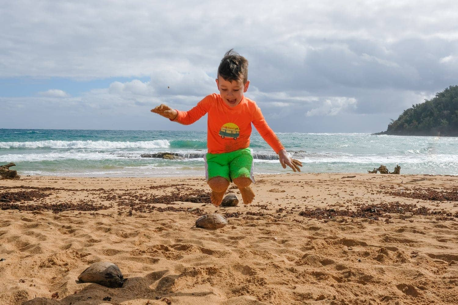 Boy jumping on Kauai beach