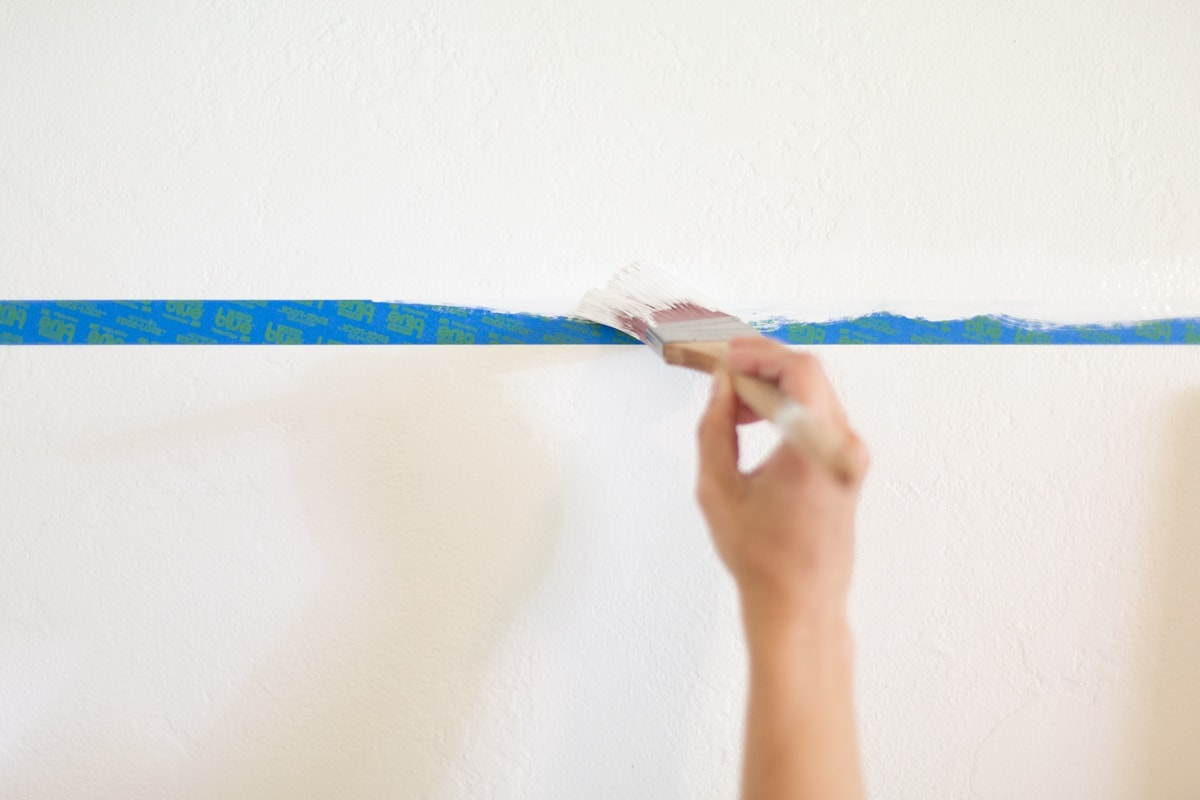 Hand brushing white paint on painter's tape