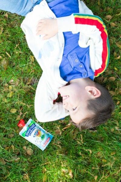 Little boy laying on grass