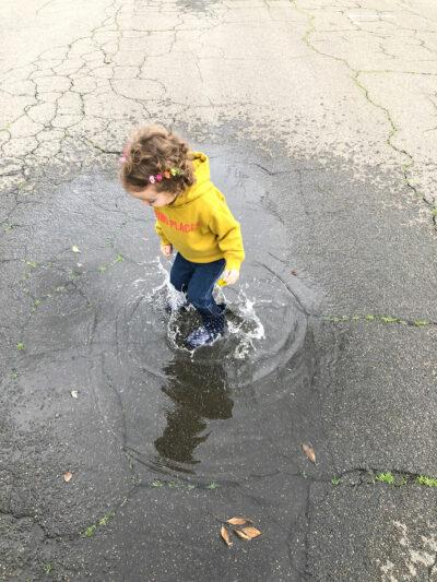 Little girl splashing in puddles
