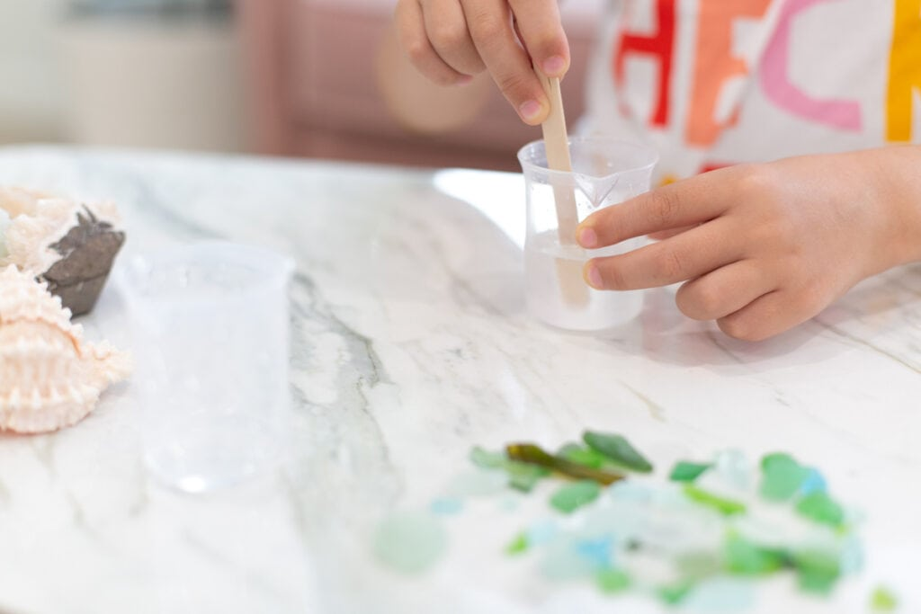 child's hands stirring resin