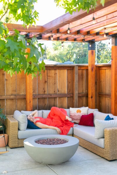 laying on outdoor couch under pergola
