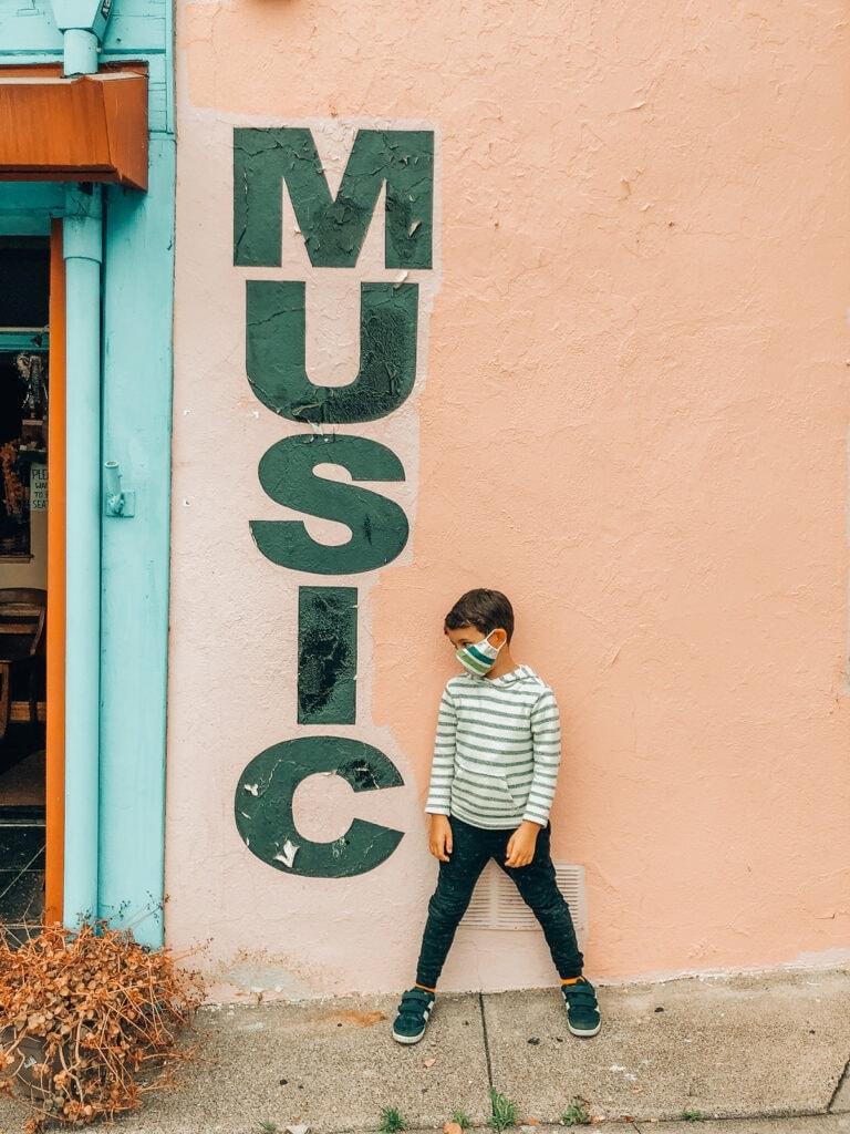 boy next to music sign