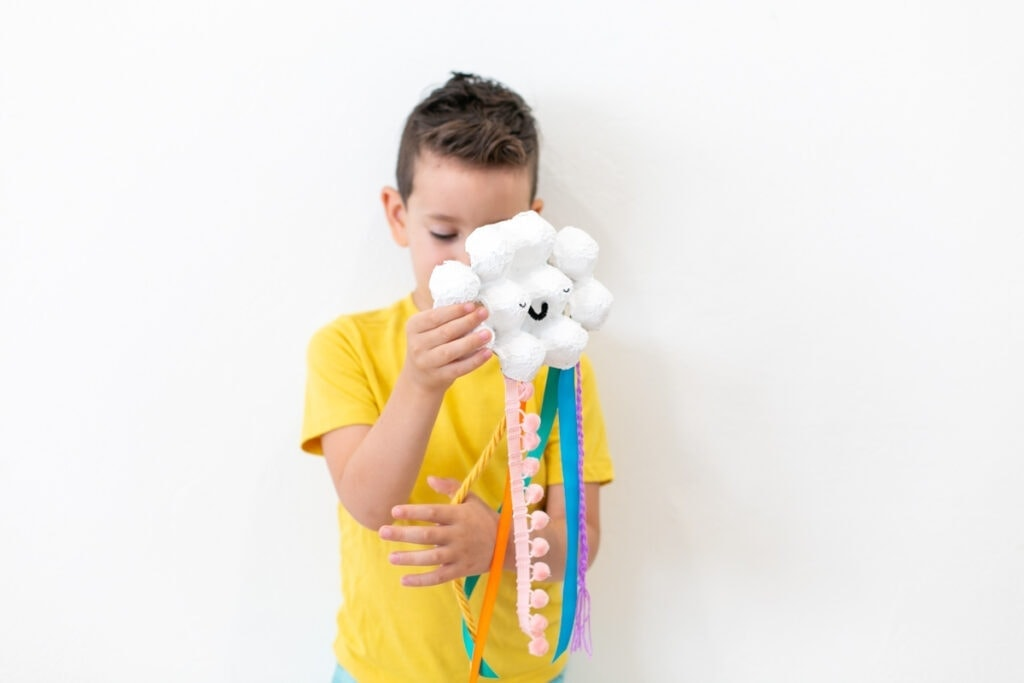 boy playing with rainbow craft