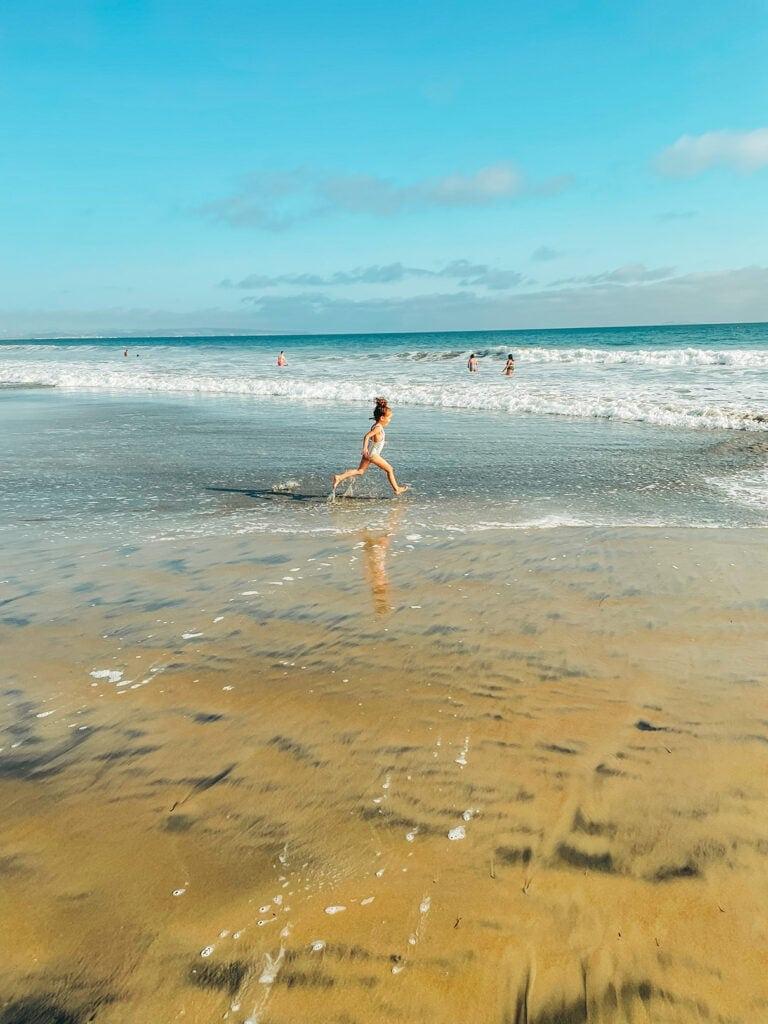 girl running on coronado beach in san diego